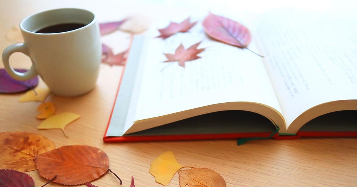 テーブルの上にある本とコーヒーと紅葉