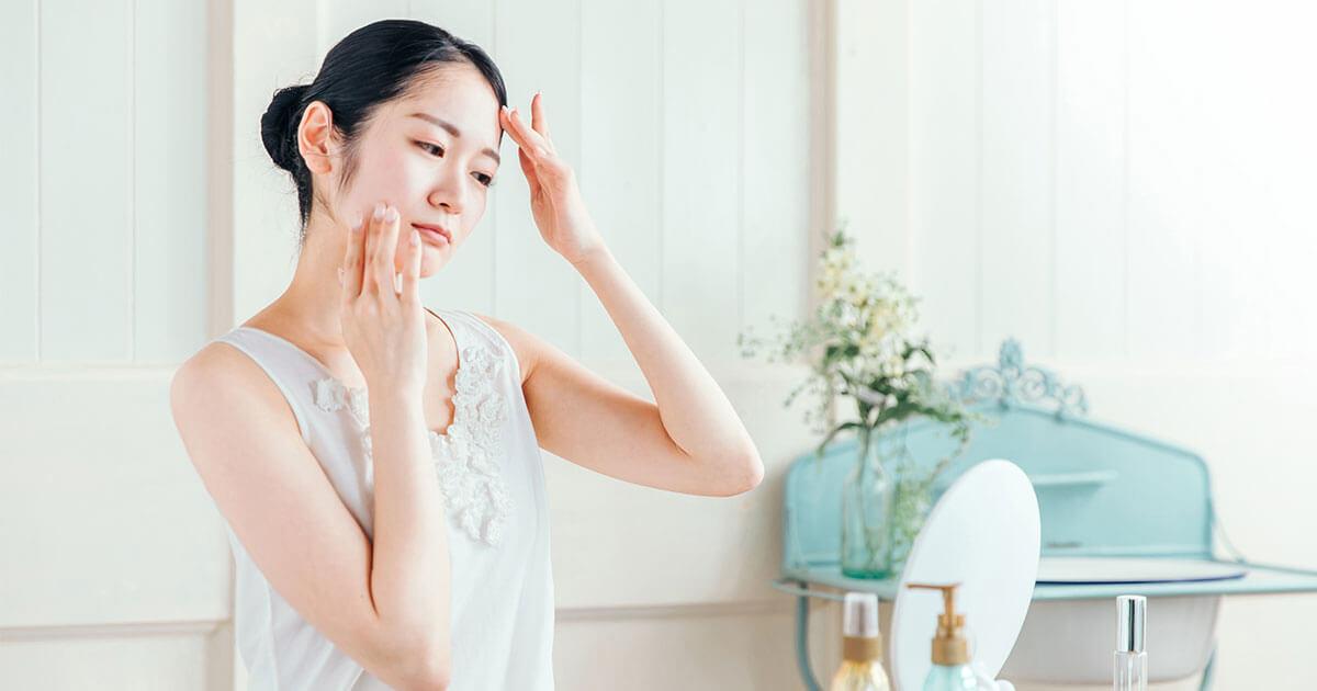 肌荒れを気にして鏡を見る女性